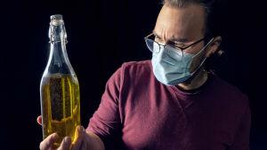 Eero Mäntymaa pitää kädessään oliiviöljypulloa