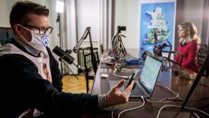 Päivi Räsänen Kristillisdemnokraattien striimaustudiossa. Etualalla puoluesihteeri Asmo Maanselkä fasilitoimassa lähetystä.