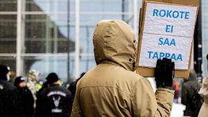 """En demonstrant håller upp en skylt där det står """"Ett vaccin får inte döda"""" under en coronademonstration i Helsingfors i mars 2021."""