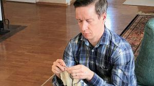 Markus Haakana stickar en tröja.