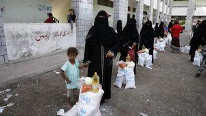 Familjer i hamnstaden Hodeidah köar för mathjälp. Över 80 procent av jemeniterna är numera helt beroende av omvärldens hjälp.