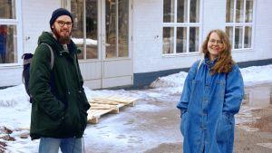 en man och en kvinna framför ljus byggnad och snö