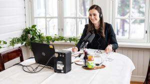 Statsminister Sanna Marin sitter vid en dator med hörlurar på. Hon intervjuas.