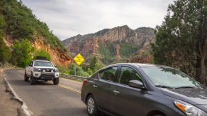 Två bilar kör längs en sliten landsväg i USA