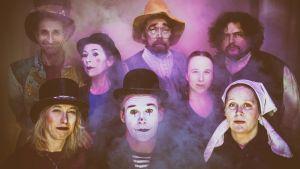 Åtta skådespelare i gammaldags kläder tittar in i kameran.