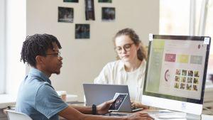 Man och kvinna vid datorer.
