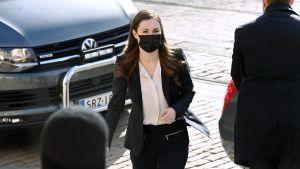 Marin i munskydd och kostym på gatan utanför Ständerhuset.