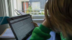 Skolelev i grön huvtröja sitter vid en dator.