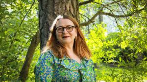 Litteraturvetaren, författaren Agneta Rahikainen i ett somrigt lövskogslandskap.