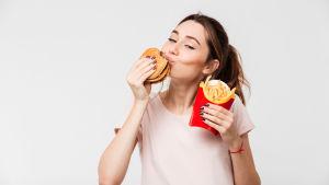Leevde kvinna med hamburgare och pommes i händerna