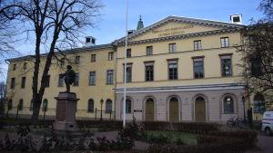 Åbo hovrätt består av en stor gul byggnad i tre våningar. Framför huset står en staty i parken.