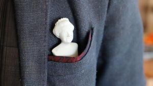 En figur som föreställer drottningen av Storbritannien. Figuren är placerad i bröstfickan på en kavaj.