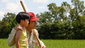 Jacob (Steven Yeun) står med sin David (Alan S. Kim) vid en åkerkant. Jacob ser glad och nöjd ut.