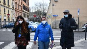 Tre personer i munskydd går längs en gata.