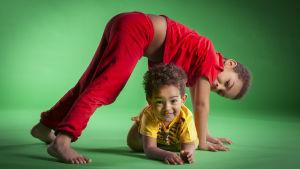 En två-årig pojke klädd i gult ligger på gålvet. En sex-årig pojke klädd i röd på honom. De ler.