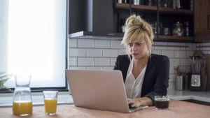 Förbryllad kvinna sitter i köket och läser något på sin dator