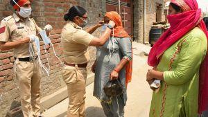 Kvinnor får munskydd inför en taxiresa till ett vaccineringscentrum