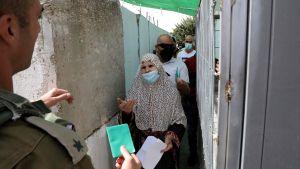 Palestinier måste visa upp identitetsbevis då de ska ta sig in i Jerusalem för att delta i fredagsbönen under muslimernas heliga månad ramadan