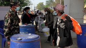kroppstemperaturen mäts på migrantarbetare som kommer till Nepal från Indien