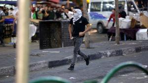 En maskerad man tar sats för att kasta en sten