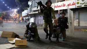 Tre personer i militärutrustning med tunga vapen.
