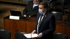 En man i kostym och munskydd.