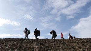 Människor som går på en upphöjd mur av sand. Himlen är blå och några tunna moln.