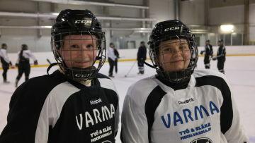 TPS ishockeydamer Matilda Eriksson och Hanna Brofelt i närbild på isen med andra spelare i bakgrunden