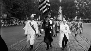 Ku Klux Klan marssii lippukulkueena Washingtonissa. Yhdysvaltain kongressin kupoli kohoaa taustalla.