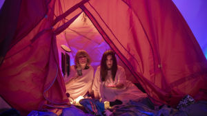 Två kvinnor i vita klänningar sitter inne i ett mjukt upplyst tält.