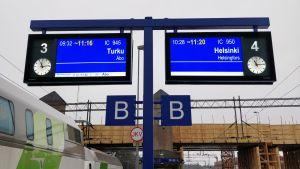 Informationstavlor visar att det är stora förseningar i tågtrafiken. Till vänster syns ett grönvitt Intercitytåg.