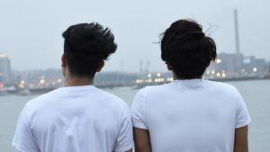 Två unga mörkhåriga killar står med ryggen i vita t-skjortor mot kameran och tittar ut över ett grått stadslandskap