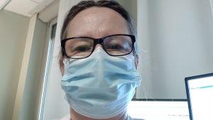 En kvinna med glasögon, läkarrock och munskydd tar en selfie.