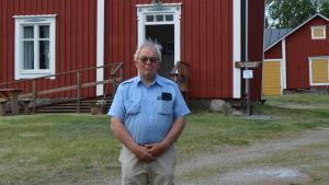 Håkan Nylund står framför ett rött hus.
