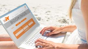 Kvinna använder en dator för att boka flyg på en sandstrand.