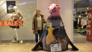 Camilla Hackman står bredvid en av sina stora säla, vid ett skyltfönster i KOP-kolmio i Åbo.