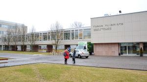 Två studerande pratar med varandra framför Åbo universitets huvudbyggnad i höstväder.