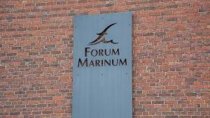 En skylt med Forum Marinums logo mot en tegelvägg.