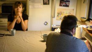 Man och kvinna sitter vi ett köksbord utan att kommunicera.