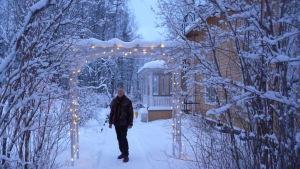 Hans Wikström utanför sitt gula egnahemshus i centrum av Tenala. Vinter och snö.