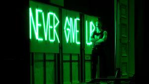 "Orden ""Never Give Up"" i neonskrift i Svenska teaterns uppsättning av ""Titanic""."