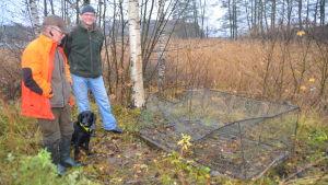 Carl-Johan Jansson och Marco Lehtikangas står bredvid en söndrig mårdhundsfälla med labradoren Fanny.