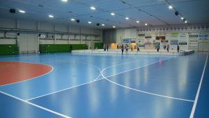 En idrottshall med blått golv. Elever spelar innebandy i bortre ändan av salen.