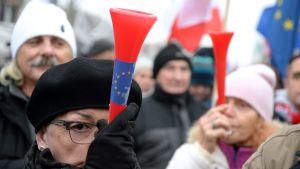 Polacker demonstrerar mot regeringen. På demonstrationen syns Polens och EU:s flaggor.
