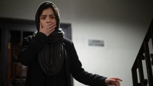 Rani står i trappan med handen framför munnen av rädsla.