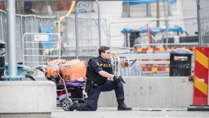Polis med draget vapen i Stockholm.