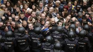 Kravallpolis står i vägen för en folkmassa som försöker ta sig till vallokaler i Katalonien.