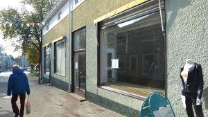 en man går brevid ett skyltfönster som är tomt.