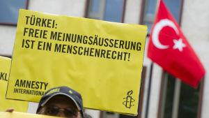 """""""Yttrandefrihet är en mänsklig rättighet"""" står det på Amnesty-aktivistens plakat"""