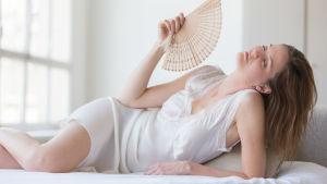 Kvinna blundar och fläktar med en solfjäder